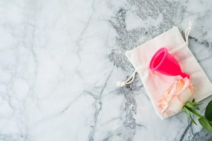 pink-menstrual-cup-with-cotton-bag-on-marble-table